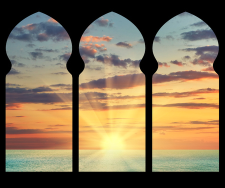 Silhouette arches inside the building of the mosque in the background of the sea sunset