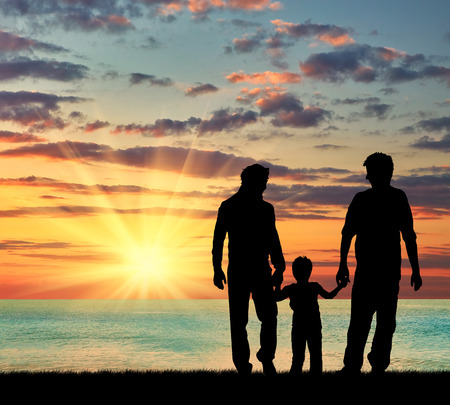 oncept: ?oncept of gay parents. Silhouette of parents of gays and baby boy walking near the sea at sunset Stock Photo