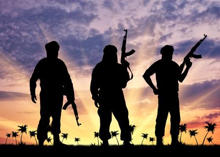 three palm trees: Concept of terrorism. Silhouette of three terrorists with a weapon against a background of sunset and palm trees