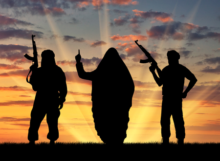terrorists: Concept of terrorism. Silhouette of three terrorists with weapons dictate their terms at sunset