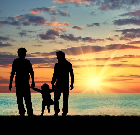 oncept: ?oncept of gay parents. Silhouette of parents of gays and baby girl walking near the sea at sunset