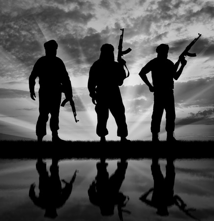 Concept of terrorism. Silhouette of three terrorists with weapons at sunset with reflection in water