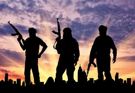 Concepto de terrorismo. Silueta de tres terroristas con un arma en un contexto de una puesta de sol en la ciudad