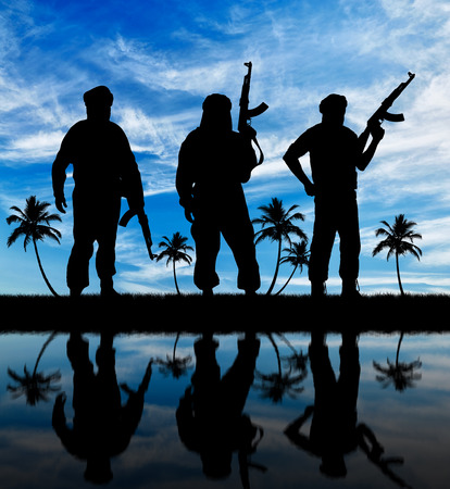 three palm trees: Concept of terrorism. Silhouette of three terrorists with a weapon against a background of blue sky and palm trees reflecting in the water
