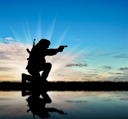 corpses: Silhouette of a terrorist with a rifle on a background of sky and reflection in water