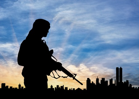 Concept of terrorism. Silhouette of a terrorist on city background at sunset