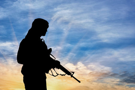 Concept of terrorism. Silhouette of a terrorist with a rifle on a background of a sunset Imagens