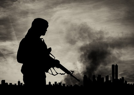 wojenne: concept of terrorism. Silhouette terrorist on city background in smoke