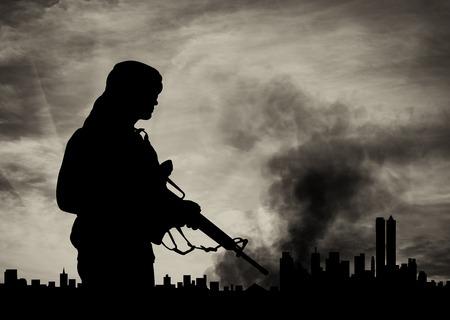 violencia: concepto de terrorismo. Silueta terrorista en el fondo de la ciudad en el humo