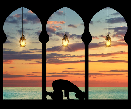 Concept of the Islamic religion. Silhouette of praying Muslim at the background of the sea sunset Фото со стока