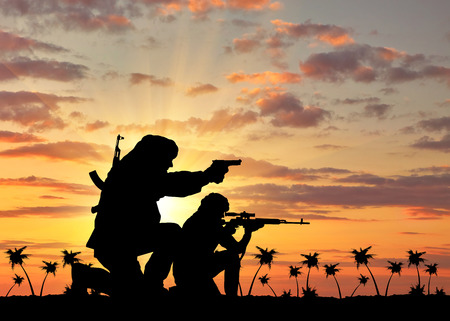 corpses: Concept of terrorism. Silhouette of a terrorists with a rifle on a background of sunset and palm trees