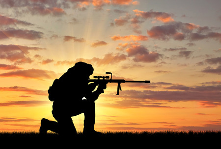 corpses: Concept of terrorism. Silhouette of a terrorist with a rifle on a background of a sunset Stock Photo