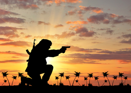 corpses: Concept of terrorism. Silhouette of a terrorist with a rifle on a background of sunset and palm trees Stock Photo