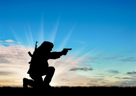 corpses: Concept of terrorism. Silhouette of a terrorist with a rifle on a background of sunset Stock Photo