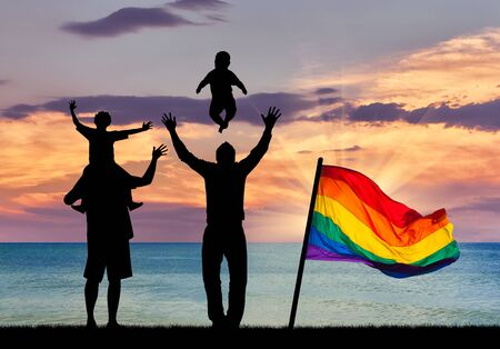Concept of gay parents. Silhouette of happy gay parents with children on the background of sea sunset and a rainbow flag