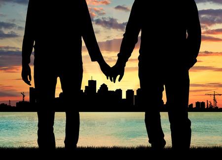 Konzept von Homosexuell Menschen. Silhouette glücklich Homosexuell Männer, die Hände vor dem Abend Meer Sonnenuntergang und die Stadt hält