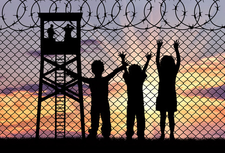illegals: Concept of refugee. Silhouette of the hungry children of refugees at the border fence at sunset and watchtower