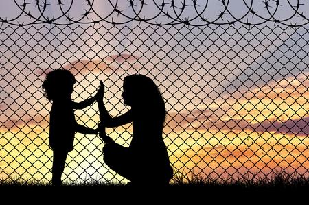 난민의 개념입니다. 석양에 테두리 울타리에 어머니와 아이 난민의 실루엣 스톡 콘텐츠