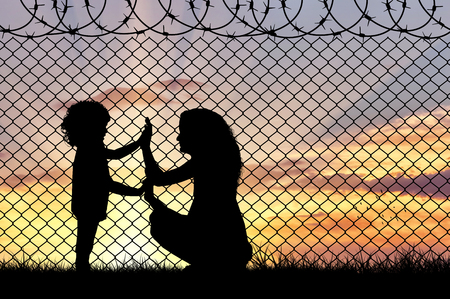 Concept of refugee. Silhouette of mother and child refugees at the border fence at sunset Archivio Fotografico