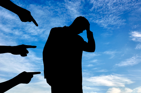condemnation: Concept of deceit and betrayal. Silhouette of man and condemning the hands of people against the sky