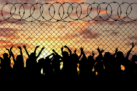 middle east crisis: Concept of the refugees. Silhouette of a crowd of refugees at the border at sunset