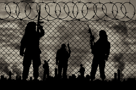 terrorists: Concept of terrorism. Silhouette terrorists near the border fence in the background on the city in smoke at sunset