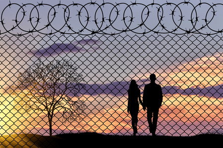 illegals: Concept of refugee. Silhouette family of refugees near the border fence in the sunset