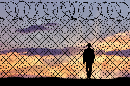 illegals: Concept of refugee. Silhouette of refugee near the border fence in the sunset