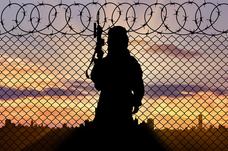 Concept of terrorism. Silhouette terrorist near the border fence in the background of the city at sunset