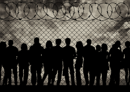 illegals: Concept of the refugees. Silhouette of a crowd of refugees at the border at sunset