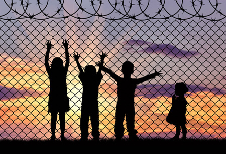 Concept of refugee. Silhouette of the hungry children of refugees near the border fence in the sunset Stockfoto