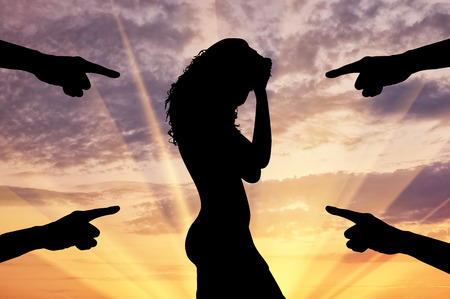 convicted: Concept of deceit and betrayal. Silhouette of a woman and condemning the hands of people at sunset