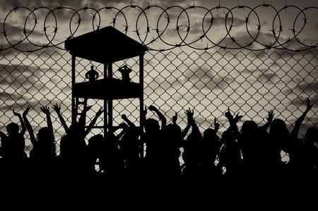 prison: Concepto de los refugiados. Silueta de una multitud de refugiados en la frontera en contra de la puesta del sol y la torre de guardia Foto de archivo