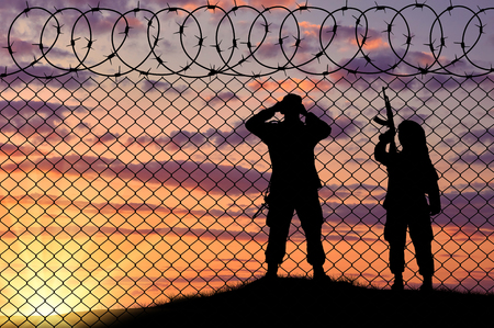 terrorists: Concept of terrorism. Silhouette scouts terrorists near the border fence in the sunset