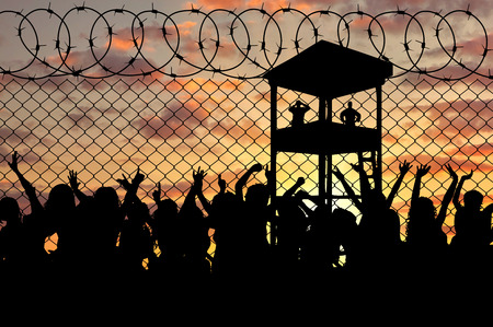 middle east crisis: Concept of the refugees. Silhouette of a crowd of refugees at the border against the sunset and the guard tower