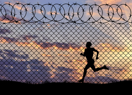 middle east crisis: Concept of refugee. Silhouette of running a refugee at the border fence at sunset Stock Photo