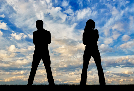 wretched: Concept of betrayal and treason. Silhouette of man and woman in a quarrel at sunset Stock Photo