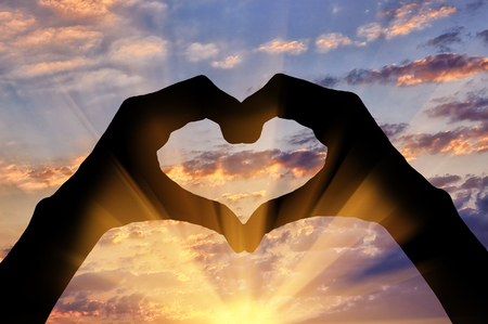 感情と感情の概念。夕日に対して心の手ジェスチャーのシルエット 写真素材