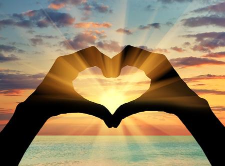 Pojęcie uczuć i emocji. Sylwetka serca gestem dłoni na tle morza o zachodzie słońca
