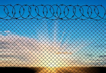 Concepto de seguridad. Silueta de alambre de púas contra un hermoso cielo