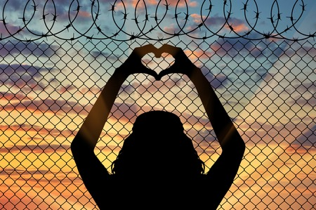 illegals: Concept of the refugees. Silhouette of a refugee shows a gesture from the hands of the heart on the background of the fence near the border