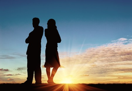 treason: Concept of betrayal and treason. Silhouette of man and woman in a quarrel at sunset Stock Photo