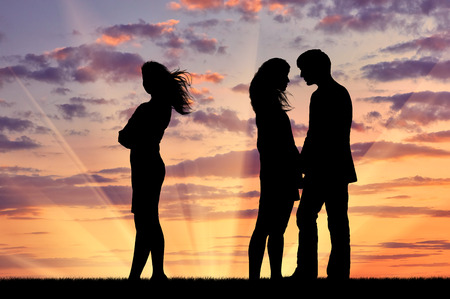 treason: Concept of betrayal and treason. Silhouette of a lonely woman near loving couple at sunset Stock Photo