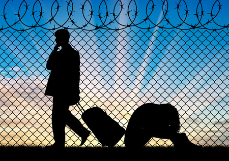 middle east crisis: Concept of the refugees. Silhouette of a couple of refugees near the border fence at sunset Stock Photo