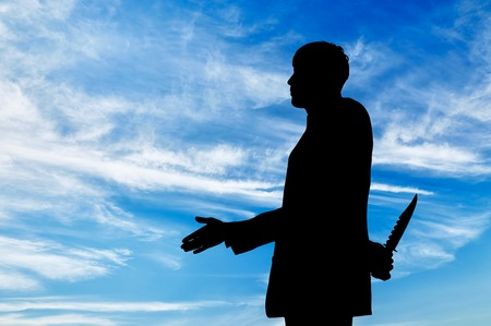 concealed: Concept of business betrayal. Silhouette of a businessman shaking hands and holding a knife behind his back