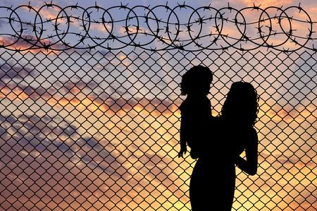 Concept vluchteling. Silhouet van moeder en kindvluchtelingen bij de grensomheining bij zonsondergang Stockfoto