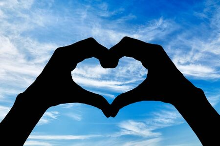 oncept: ?oncept of feelings and emotions. Silhouette of the heart hand gesture against a blue sky Stock Photo