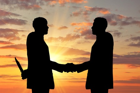 Concept of business betrayal. Silhouette of two businessmen shaking hands and keep arms behind his back weapon