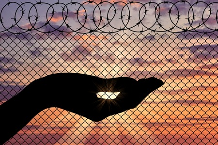 middle east crisis: Concept of emotions and feelings. Silhouette refugee arms near the border fence on the sunset background Stock Photo