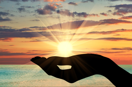 Concept of emotions and feelings. Silhouette of a hand holding the sun at sunset